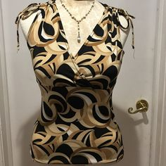 Womens patterned top Pretty black tan cream white brown pattern top with crisscross V-neck front and adjustable top sleeves with ties. Super cute to wear alone or layer with a cardigan or shrug or sweater. Dress this up or down easy to travel with packs very well. Byer California Tops