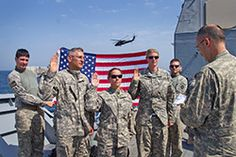 Soldiers from Alpha Company, 1-207th Aviation Regiment recite the re-enlistment oath while aboard the USS Monterey. Reciting the oath left to right are Sgt. 1st Class George Koval, Sgt. 1st Class Julie Small and Sgt. Amber Hillman. 1st Lt. Dean Burgess and Capt. Bradley Hoppes are holding the flag. Chief Warrant Officer 2 Terry Symonds, far right, recites the oath of enlistment. (U.S. Army photo by Sgt. Mark Scovell)