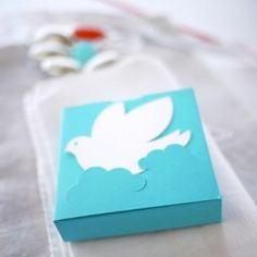Cette boîte est un carré plat, collé, coloré, qui s'ouvre sur la tranche. Sa face porte une découpe de deux nuages, qui accueillent une silhouette de colombe...