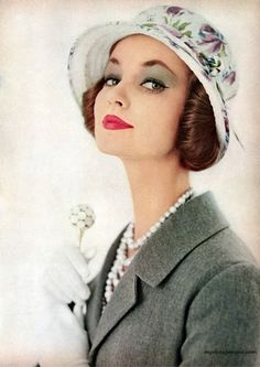 Grey-blue eye shadow and fruit punch pink make-up this beautiful 1950's model is sporting.