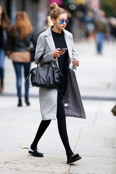 Gigi Hadid looks chic post-ballet class in a leotard, tights, gray coat, slides, mirrored aviator sunglasses, and a leather duffle handbag