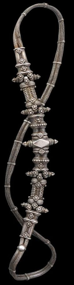 Silver braided wire belt (Karmapatti) from  Maharashtra/Andhra Pradesh, India circa late 19th century. The belt opens by means of a screw mechanism - one of the two finials that jut from either side of the most central panel element of the belt screws out allowing the belt to be opened so that the wearer can place it about the hips.