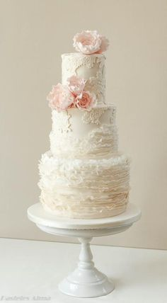 This wedding cake design incorporates vintage, romance and modern styles perfectly together. We love the on-trend deep tiers covered with delicate fondant frills and detail lace pieces. The blush pink sugar roses add just the right amount of color too. #ManAboutCake