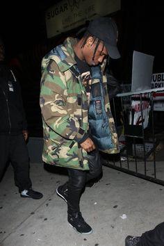 Travis Scott wearing Supreme Uptown Parka 700-Fill Woodland Camo, Jordan Eminem x Carhartt x Air Jordan 4, Off-Brand Travis Scott Madness Tour Cap, Balmain Slim Fit Leather Sweatpants