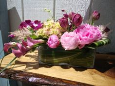 Modern centerpiece with pink flowers in a low glass rectangle vase