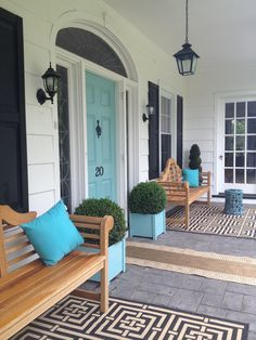Front porch design with chippendale benches, turquoise front door and planters. Love the door color!