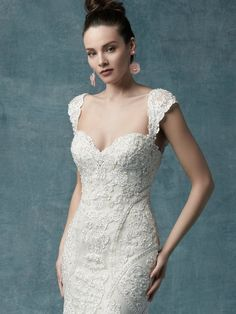 This vintage-inspired wedding gown features a bodice of pearls and beaded lace motifs, drifting into a tulle fit-and-flare skirt. Delicate lace motifs adorn the strapless sweetheart neckline. Finished with covered buttons over zipper closure and inner corset. Cap-sleeves accented in beaded lace motifs sold separately.