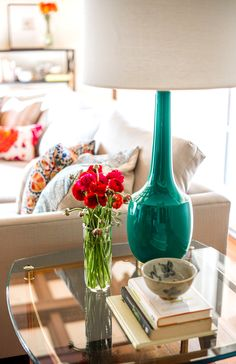 Emerald lamp on side table in neutral living room with colorful pillows and flowers