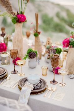A bohemian tablescape with fuchsia flowers in a gold and brown setting.