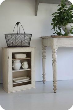 Vintage wire basket, white pitchers, old cabinet, old table.  Like everything in this pic!