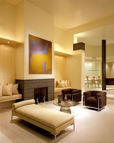 Warm lighting makes this modern beige living room inviting, with a pair of…