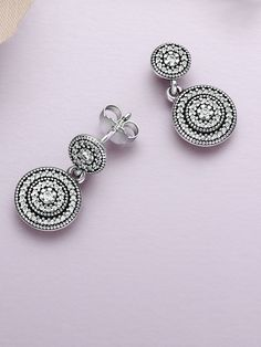 Two discs encrusted with concentric circles of sparkling stones add a glamorous expression to these elegant drop earrings. With their classic look, they will add vintage sophistication to any occasion. #PANDORA #PANDORAearrings