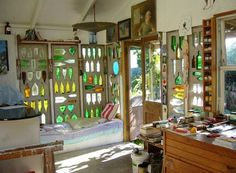 An artist's studio in New Zealand, featuring recycled glass bottles set into a cob-built wall. I LOVE this.
