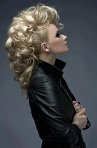 """Giant fauxhawk  (start by setting the hair in 1"""" curls. Once cool, take down the curls, and part the hair vertically into 3-5 triangular sections. Comb each section up and to the middle, secure with an elastic (creating a Mohawk with ponytails). Then use your fingers to spread curls about each pony, bobby pinning pieces here and there to cover the ponytails and create a wider Mohawk.)"""