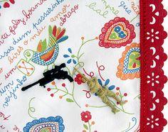 Bai feliz buando, no bico dum passarinho n° 3   (série Portugal - lenços de namorados)   de Fábio Carvalho   tecido estampado, bico de renda e passamanaria industrial, bordado à mão, armas e soldados de plástico de brinquedo   2012   55x75 cm