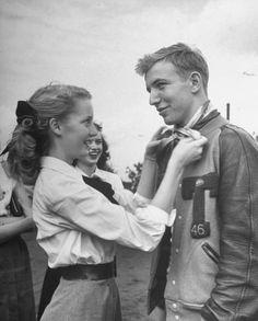 Teen Fads ,1947 Girl ties her hair scarf around her boyfriends neck as a fond token. Boy often gives football sweater as token to his girl.