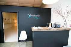 Reception Area - Demising wall with glass door. Built-in reception desk. Like the charcoal color and adhesive sign behind the front desk.