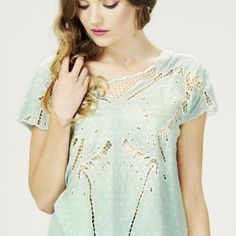 This crepe-y embroidered blouse is as delicate and intricate as a butterfly's wings, and features a striking cut-out design of just that! This pretty pastel turquoise piece will simultaneously illuminate and fascinate.