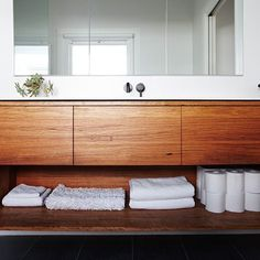 Integrated Corian vanity top with bowl, mirrored shaving cabinets, recycled solid blackbutt timber with finger pull recess #cosinteriors #cabinets #mirroredcabinet #mirror #blackbutt #timber #timbervanity #timberbathroom #vanity #vanityinspo #bathroom #bathroomdesign #instainteriors #instabathroom #recycledtimber #recycle #ecotimber #ecofriendly