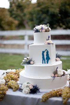 A four-tier white wedding cake with flowers and dancing bride and groom silhouette