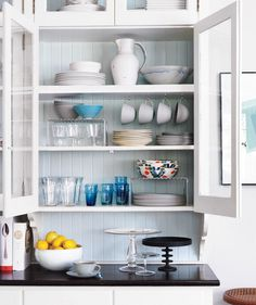 Make use of all your shelf space by hanging a row of coffee cups and using metal risers to add an additional layer.