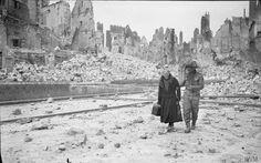 TRES BELLE PHOTO .......  .  La bataille de Normandie: Un soldat britannique à Caen après sa libération, donne un coup de main à une vieille dame entre la scène de dévastation totale. La ville avait été en grande partie détruite lors du bombardement, laissant un grand nombre de sans-abri de la population