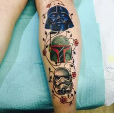 Funny cartoon like colored various Star Wars heroes helmets tattoo on leg combined with flowers