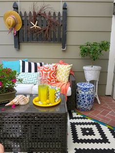 To punctuate your outdoor space start with neutral furnishings and pillows or rugs that pop with color; next add shade, wall art and flower pots or garden stools.