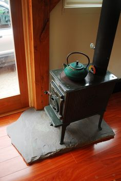 Up until now weve just been using a spare piece of stone to rest our wood stove on. This week we went to our local hard-scaping store and picked out a piece of slate for the hearth. The piec Wood, Shed Plans, Hearth, Small Wood Stove, Cabin Homes, Pellet Stove Hearth, Stove, Hearth Stone, Modern Fireplace
