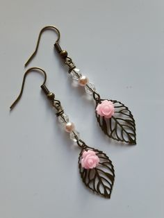 Pretty Bronze Leaf Drop Earrings        Pretty and Feminine Design in filigree metal    Leaf theme perfect for any occasion          24mm bronze tone slim veined filigree leaf charms  Pink rose cabonchon  4mm glass pink pearl  4mm faceted glass bicone beads  Bronze hooks with comfort stoppers  Overall drop approx 50mm       | Shop this product here: http://spreesy.com/Flossiesjewelsngifts/4 | Shop all of our products at http://spreesy.com/Flossiesjewelsngifts    | Pinterest selling…