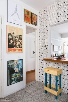 Cozinha com papel de parede de bolinhas e galeria com quadros trazidos de viagem.