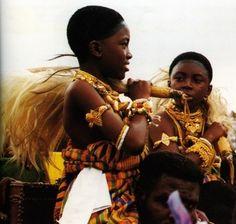 Ashanti Royal girls being carried shoulder high wearing regal Kente cloth