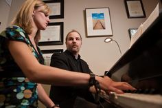 A student rehearses at the piano with faculty composer Blake Henson (Music).