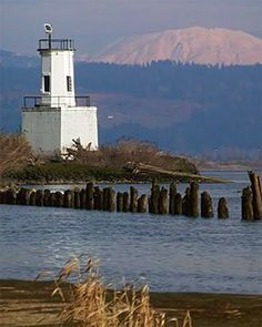 Lighthouse near Warrior Rock on the Columbia River, OR: Mt. St. Helens in background Originally a two-story structure, the lighthouse was built in 1889