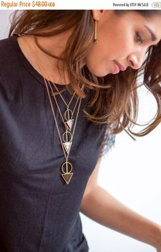 A stone triangle bead hangs in a brass geometric setting from new brass chain. All parts are able to spin around. Pendant is 2 long and 1 at the widest point. Choose between a 24 or 30 chain. Current stone options are dalmatian jasper and onyx. *The bottom necklace is the 24 length pictured on the model. The shorter 2 are just to show the color options.   Care: keep dry and clean with a jewelry cloth to protect the finish. *A sunshine jewelry cleaning cloth is included with this purchase to…