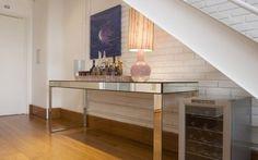 A mesa espelhada, dá um toque moderno ao bar debaixo da escada. Foto: Divulgação