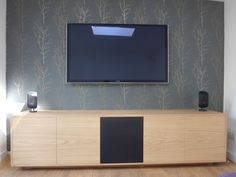 """Oak TV/AV unit featuring a central speaker cloth door, push to open doors and adjustable shelves. The cabinet has mitred corners and the grain runs through the doors for a seamless finish. Sat on a """"floating"""" plinth and featuring cable management it provides a stylish solution to all your storage needs."""