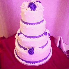 Each tier has beautiful flowers that are in white and purple made out of butter cream. Purple ribbon going at the base of each tier.