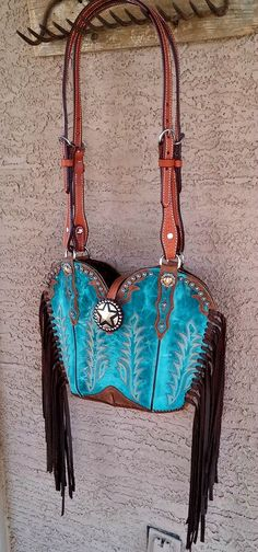 Turquoise Boulet cowboy boots made into a western purse with fringe. Handle is made from horse bridle headstall. Made in USA #cowboybootpurse #westernpurse #westernbag #cowgirlfashion #cowgirlswagger #madeinusa #diamond57