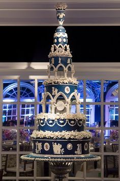 This ornate five-tiered wedding cake is decorated in blue and white, with columns, flowers, and white fondant vignettes.