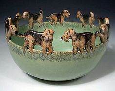 This field of Airedales look like they're working out the social dynamics of the group. Who will lead the chase that's sure to follow? This carved rim stoneware bowl is by Nan Hamilton.