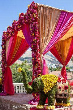 A vibrant floral mandap for an outdoor wedding.