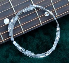 Recycled Guitar String Bangle with Glass Beads Gift for Musician or Music Lover. $22.00, via Etsy.
