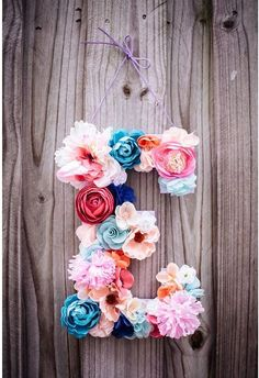 Silk artificial flowers adhered to letter to create pretty door or room wall decor, initial monogram.