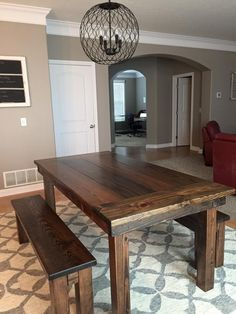 "James+James 6'x37"" Farmhouse Table with a traditional top with endcaps and all stained in Dark Walnut. Pictured with matching Farmhouse Bench.    Gray and white rug dining room chicken wire chandelier globe open floor plan rustic farm table"