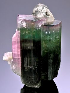 Gemmy crystal of tri-colored Elbaite with a Quartz at top! This fat crystal begins with a dark green base.  The dark green changes over to an pretty grassy-green near its midpoint and eventually to a raspberry-pink at the top termination. This specimen has a lot going for it for the size, including a pink Tourmaline attachment along the left side. Measures 4.7 cm by 3.5 cm by 3 cm in total size. Listed Price $895