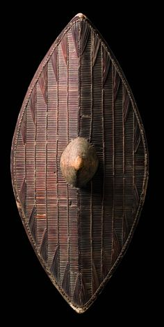 Africa | Shield from the Ganda people of Uganda | Wood frame with animal skin rim, woven cane | Such shields were carried by the Ganda north of Lake Victoria and the Soga in the district of Busoga to the northeast of the Lake. On account of the high artistic quality of their workmanship and their elegant wickerwork ornamentation, many of these shields had already come into the possession of European museums before the turn of the 19th century.