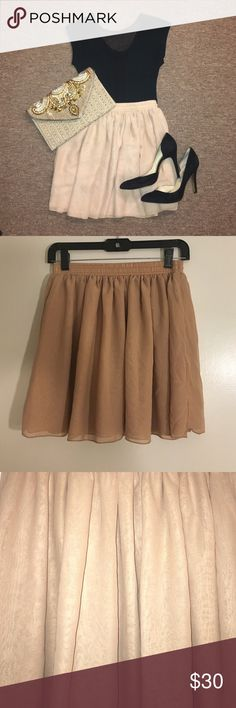 """Beautiful """"Chiffon"""" by American Apparel Skirt Gorgeous, very versatile beige/nude American Apparel miniskirt- can wear in so many ways!! Dressed up like in cover photo or dressed down with a white tshirt and converse sneakers! Size M/L. No stains and only had been worn 2/3 times, love it it's just a little big on me. Double layered, slightly sheer but not see through. Very light, airy and comfortable. 100% polyester. Elastic waistband. Color looks different in different light but it's…"""