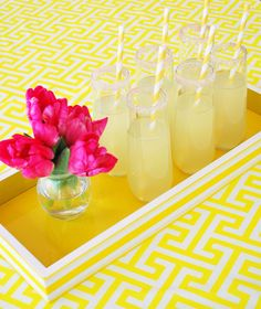 Summer entertaining idea - yellow serving tray, yellow tablecloth and a bright bouquet of flowers to offset.