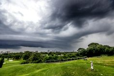 A golfer stands on the 5th tee at Moore park Golf Course as the storm front moves in over the Sydney skyline.
